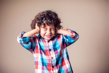 Young boy with covering his ears with hands.Children and emotions concept Foto de archivo - 131288443