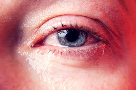 Close-up blue eye of a woman with a tear. People and emotions concept 写真素材