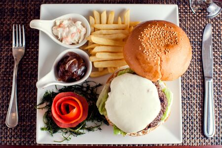 Large tasty burger with French fries in a cafe on a white plate
