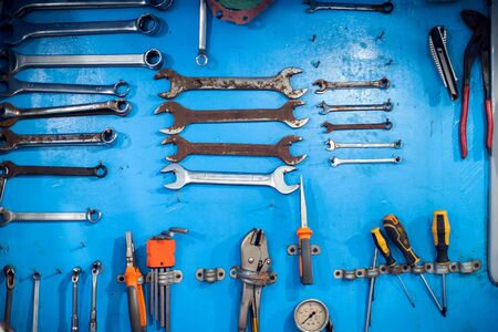 A lot of different wrenches on the blue wall background Imagens