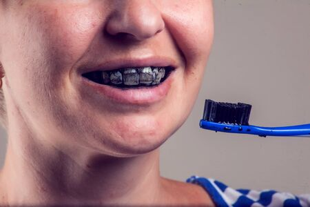 Woman cleans her teeth with charcoal toothpaste. People and healthcare concept.