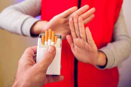 Quitting smoking concept. Hand is refusing cigarette offer. Stop smoking and healtcare concept Standard-Bild