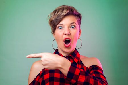 People and emotions - surprised young woman show with finger on something