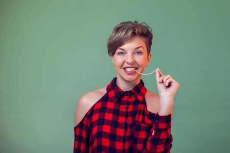 People and emotions - a portrait of smiling young woman with short hair playing with chewing gum 写真素材