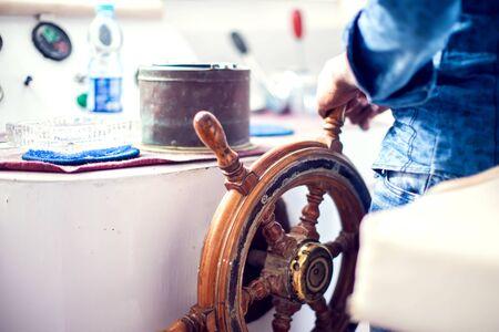 Die Hände des Kapitäns und ein Steuerrad Bootshafendienste