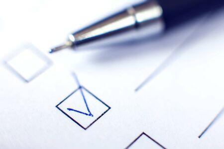 Liste de contrôle avec un stylo sur du papier blanc. Notion de case à cocher. Banque d'images