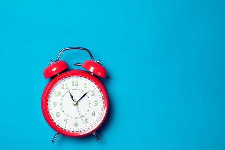 Red alarm clock on the color background.