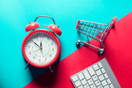 Red alarm clock, shopping trolley and keyboard on the doubble color background. Online shopping and sales concept