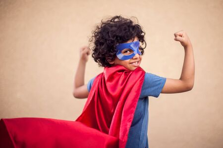 A portrait of kid boy with curly hair in costume of superhero. Childhood and success concept