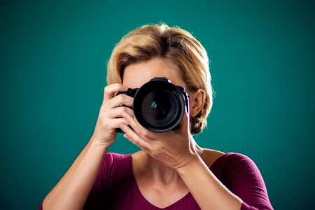 Smiling pretty woman with short blond hair holding photo camera. People, hobby and lifestyle concept