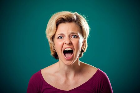 Angry woman with short blond hair in front of green background . People and emotions concept