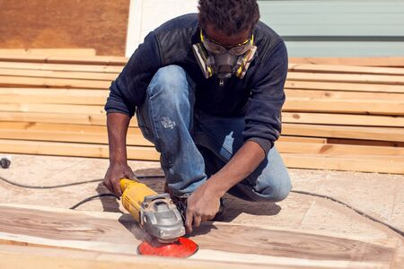 A handyman in mask polishing wooden plank outdoor.