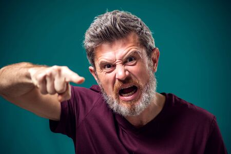 A portrait of angry bearded man in red t-shirt pointing finger at camera. People and emotions concept
