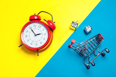 Red alarm clock, small shopping trolley on color background. Shopping concept Stock fotó