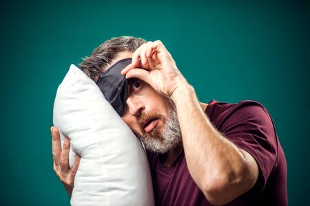 Man in red t-shirt and sleep mask on head holding white pillow. Lifestyle and bed time concept Imagens
