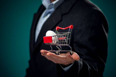 A portrait of bearded man in suit holding small shopping trolley with white egg inside. Business and finance concept