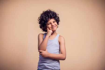 A portrait of pensive kid boy with curly hair. Children and emotions concept