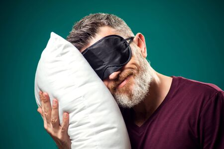 Man in red t-shirt and sleep mask on head holding white pillow. Lifestyle and bed time concept Imagens - 148274715