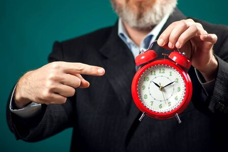 Bearded businessman in suit holding red alarm clock and pointing with a finger at it. Time management concept