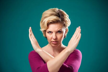 Angry woman with short blond hair showing stop gesture. People, lifestyle and emotions concept