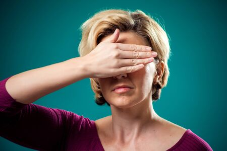 Woman with short blond hair covering her eyes with hand. People, lifestyle and emotions concept Stockfoto