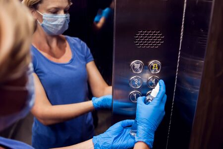 Woman with face medical mask and blue gloves doing disinfection of buttons in elevator. Hygiene and health protection concept Banque d'images