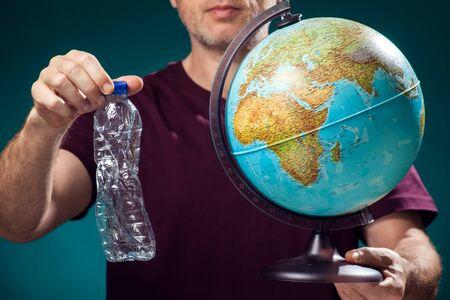 Ein Mann, der einen Globus und eine zerknitterte Plastikflasche hält. Konzept der Erdverschmutzung und des Umweltschutzes. Studioaufnahme