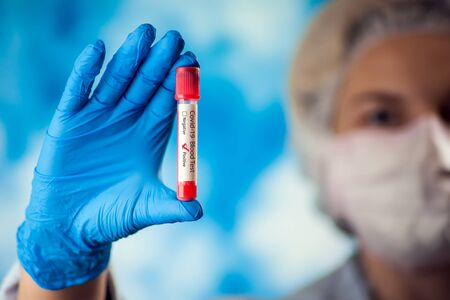 Female doctor in blue gloves and medicine mask holding test tube with blood. Covid-19. Coronavirus. Medicine, laboratory and healthcare concept