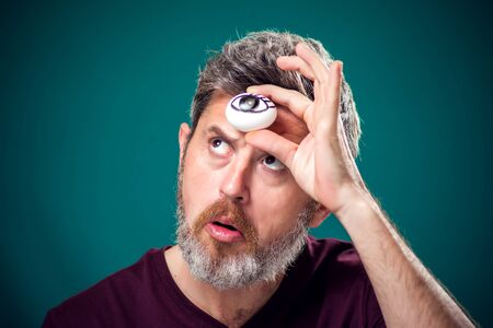 A portrait of bearded man in red t-shirt holding egg with drawing eye behind forehad as third eye symbol.