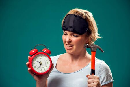 A portrait of angry woman with sleep mask on head holding hummer wanted to crush red alarm clock in the morning.