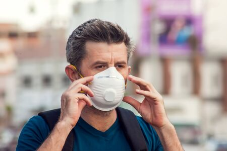 A portrait of man with face medical mask on the street. Virus protection concept