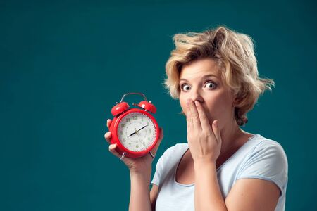 A portrait of woman with short blond hair holding red alarm clock and feeling shocked because of oversleep