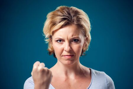 A portrait of angry woman with short blond hair showing fist at camera. People and emotions concept Foto de archivo