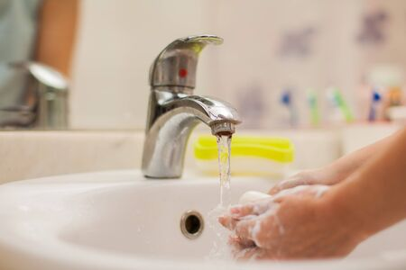 Woman washing hands with soap in bathroom. close-up shot. People and healthcare concept. Archivio Fotografico