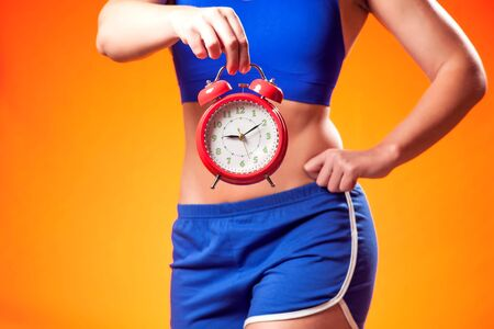 Woman in sportswear holding alarm clock. People, fitness and dieting concept