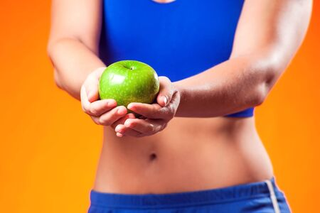 Woman in sportswear holding an apple. People, fitness and dieting concept