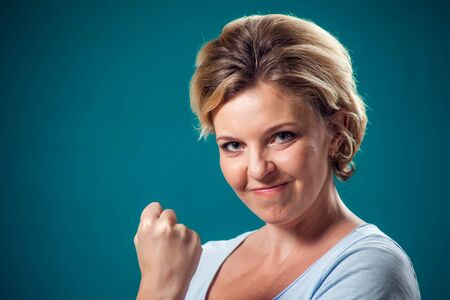 A portrait of angry woman with short blond hair showing fist at camera. People and emotions concept