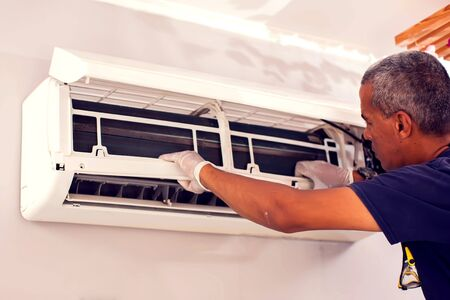 Man worker fixing air conditioning on the wall. Professional service