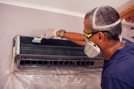 Man worker doing professional cleaning of air conditioning. Stockfoto