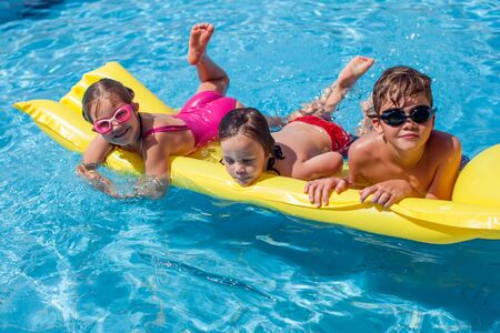 Kids playing in the swimming pool. Childhood, summer and holiday concept Stockfoto