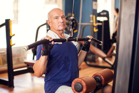 Senior man in the gym training back muscles. People, health and lifestyle concept