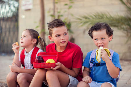Pupils having a snack outdoor. Children, education and nutrition concept