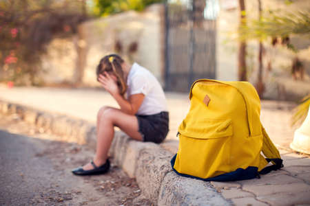 Unhappy pupil with backpack sitting outdoor. Girl feeling stress. Children and emotions concept