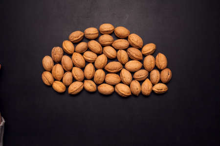 Unpeeld walnuts in the middle of black background. Organic and healthy food Stock fotó