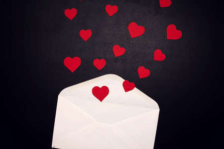 Envelope with hearts on the black background. Romance and love concept
