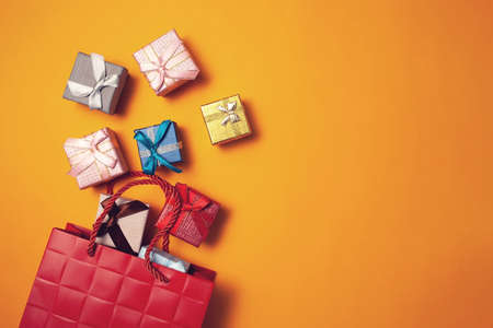 Gift boxes falling into gift bag on yellow background. Celebration, party and shopping concept