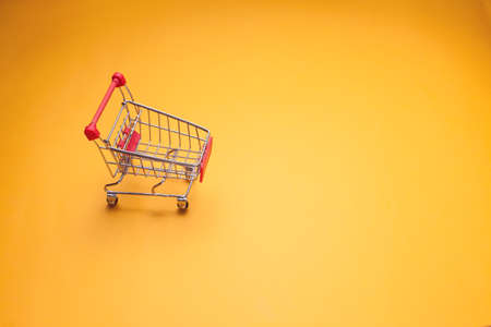Empty trolley on yellow background. Shopping concept