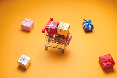 Trolley and gift boxes on yellow background. Shopping and celebration concept