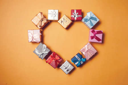 Gift boxes lying in the shape of heart on yellow background. Celebration and shopping concept