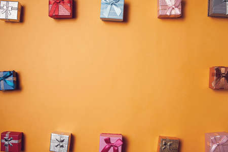 Gift boxes of different colors on yellow background. Celebration, party and shopping concept